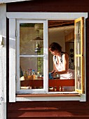 View through open window of woman in kitchen