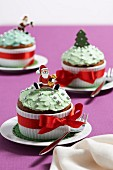 Buttercream-topped cupcakes in fluted ramekins with red ribbons, Father Christmas figure and Christmas tree