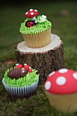 Cupcakes decorated with a ladybird, as a toadstool and with a hedgehog