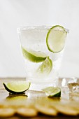 Cocktail with vodka and lime wedges