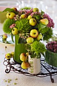 Flower arrangement with green carnations, sedum and crab apples in various vases on small wire tray
