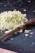 Elderflowers on a chopping board with a wooden spoon