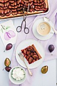 Plum cake with cream and coffee, and a picture of plums