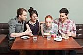 Junge Paare beim Geburtstagfeiern in einem Restaurant