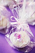 Cake pops on a purple surface, wrapped as a gift