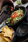 Woman Making Guacamole on Lap with Mortar and Pestle