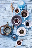 A still life featuring assorted types of tea, a teapot and a tea strainer