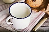 Frische Milch im Emaillebecher und Cookies auf rustikalen Holztisch