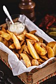 Fried potato wedges with white sauce in vintage box