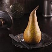 Eine Birne auf Metallteller mit Messer