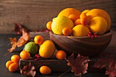 A still life featuring citrus fruits and autumn leaves
