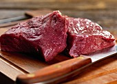 Venison steak raw on a chopping board