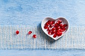 Pomegranate seeds in a heart-shaped bowl