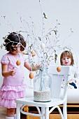 Kleine Mädchen mit Osterstrauss in einer großen Glasvase