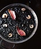 Squid ink rice with red mullet and prawns