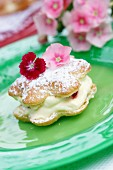 Choux pastry filled with crème pâtissière and topped with edible flowers