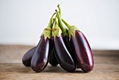 Several aubergines on a wooden table