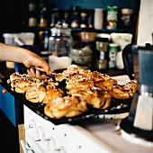 A woman taking freshly baked cinnamon buns from a baking tray
