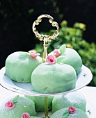 Mint-coloured marzipan cakes on a tiered cake stand