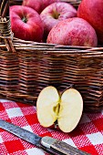 Apples (Royal Gala) in a basket with a knife on a checked picnic blanket