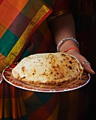 A woman holding a plate with a cheese naan (India)