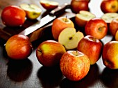 Several Braeburn apples, whole and halved