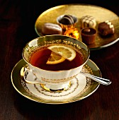 A cup of Earl Grey tea with lemon, by a plate of chocolates