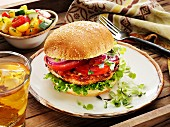 Turkey Burger with Lettuce, Tomato, Red Onion and Micro Greens on a Bun with a Grape Tomato Salad and an Iced Tea on the Side