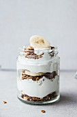 A healthy layered dessert of parfait, bananas and muesli