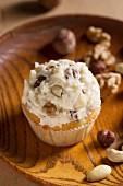 Cupcake mit Nüssen im Frosting, auf Holzteller