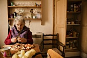 Elderly lady peeling potatoes for Spanish omelette (tortilla)