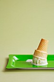 An ice cream cone with a scoop of vanilla, upturned on a green tray