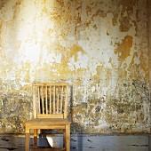 Einfacher Holzstuhl vor verwitterter Wand
