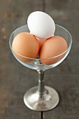 Four eggs in a glass with a stem