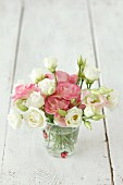 Romantic bouquet of flowers with roses and lisianthus in a glass of water