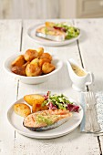 Barbecued salmon steak with bearnaise sauce, potatoes and salad leaves
