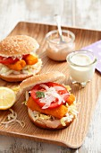 Fish fingers in a burger bun with sliced tomato and onion