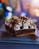 A serving of chocolate & caramel cake topped with nuts