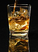 Scotch being poured into a glass with ice