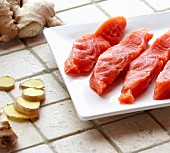 Fresh Pieces of Raw Salmon Steak on a White Plate and Fresh Ginger