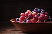 Red Seedless Grapes and Concord Grapes in an Old Wooden Bowl