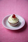 Cherry cupcake with cream icing and a glacé cherry