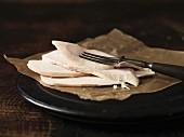 Still life of sliced chicken on waxed paper
