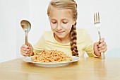 Girl with plate of spaghetti and oversized cutlery