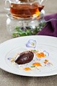 A chocolate dumpling with tea, white chocolate curls, salt and fruit compote