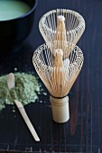 Two bamboo tea whisks, a matcha spoon and green tea powder