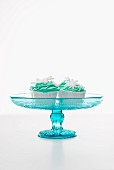 Cupcakes decorated with green icing and snowflakes, on a cake stand