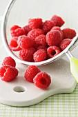 Fresh raspberries in a sieve on a chopping board
