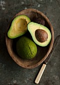 Avocados, whole and cut in half, in a wooden bowl