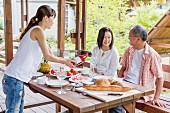 Junge Frau schenkt am Tisch auf der Terrasse ihren Eltern Wein nach
